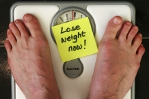 Loose weight now post-it note with feet on scale [CC]