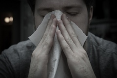 Man with a tissue suffering from allergies